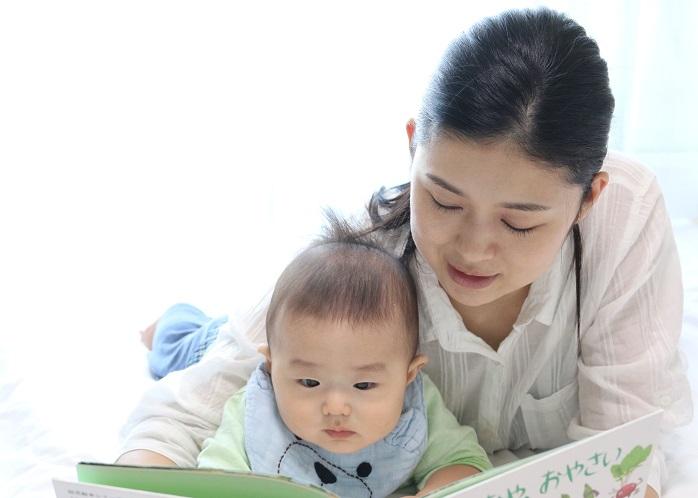 赤ちゃんに絵本を読み聞かせているお母さん