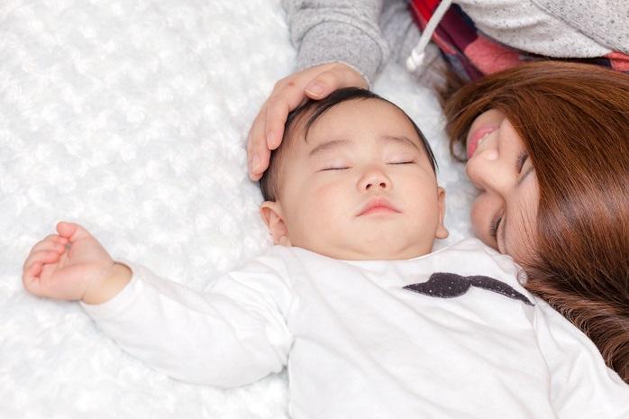 赤ちゃんを寝かせつけるお母さん
