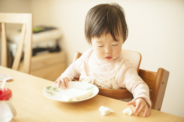 お皿から落ちた離乳食を手づかみする乳幼児